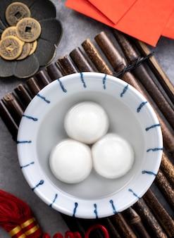 Draufsicht auf große tangyuan yuanxiao (klebrige reisknödelbällchen) für das festessen des neuen mondjahres, wörter auf der goldenen münze bedeuten den dynastienamen, den sie gemacht hat.