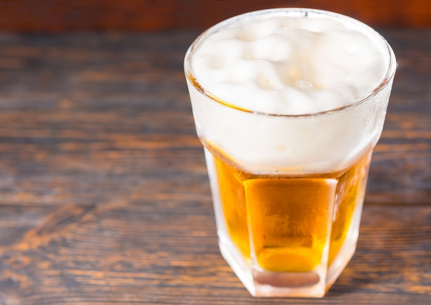 Draufsicht auf großes glas mit einem hellen bier und einem großen schaumkopf auf altem dunklem schreibtisch. getränke- und getränkekonzept
