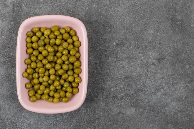 Draufsicht auf grüne erbsen in dosen in rosa schüssel über grauem tisch.
