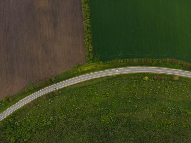 Draufsicht auf grüne felder und straße mit autos, die sich entlang der autobahn bewegen