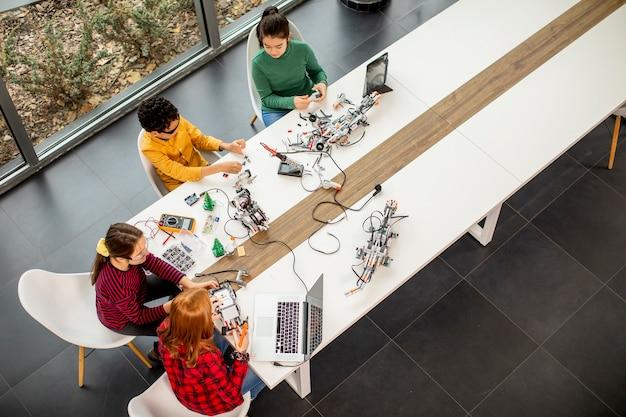 Draufsicht auf gruppe der glücklichen kinder, die elektrisches spielzeug und roboter am robotikklassenzimmer programmieren