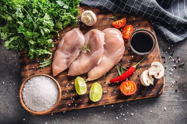 Draufsicht auf hähnchenbrust, sojasauce, pilze, tomaten, zitrone, chili, pfeffer, salz und petersilie auf einem rustikalen holzschneidebrett und schwarzmetallischem hintergrund.