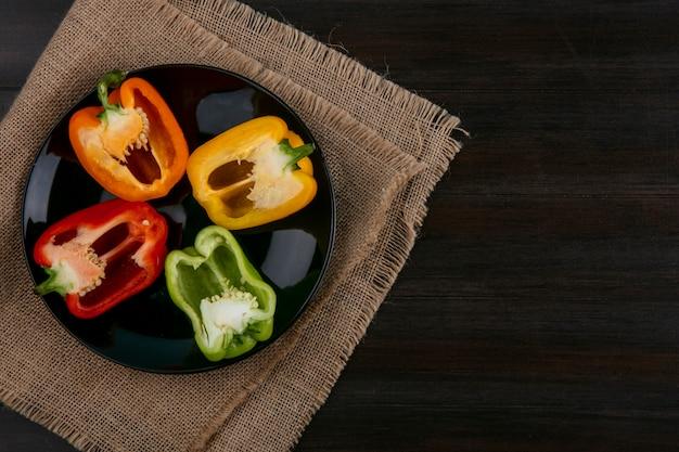 Draufsicht auf hälften von mehrfarbigen paprika auf einem schwarzen teller auf einer holzoberfläche