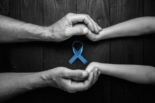 Draufsicht auf hände, die prostatakrebsband, dickdarmkrebskonzept, blaues bandsymbol halten. schwarz und weiß.