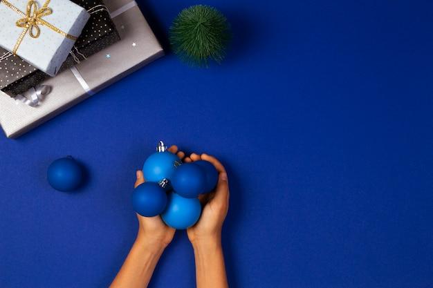 Draufsicht auf hände, die weihnachtsdekorationskugeln halten