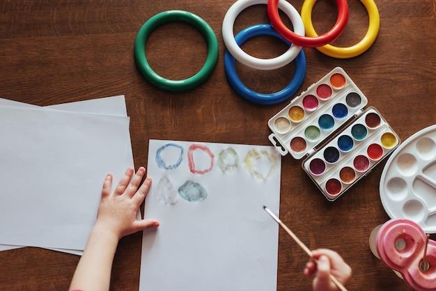 Draufsicht auf hände und pinsel malen aquarellgouache