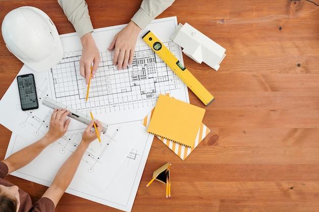 Draufsicht auf hände von zwei zeitgenössischen ingenieuren oder architekten, die skizze eines neuen bauprojekts diskutieren, das von arbeitsmaterial umgeben ist