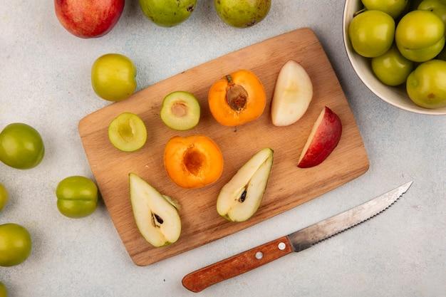 Draufsicht auf halbgeschnittene früchte als pflaumen-aprikosen-birnen-pfirsich auf schneidebrett und ganze mit messer auf weißem hintergrund