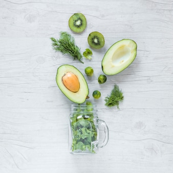 Draufsicht auf halbierte avocado; kiwi; rosenkohl und salat mit glas vor hölzernen hintergrund