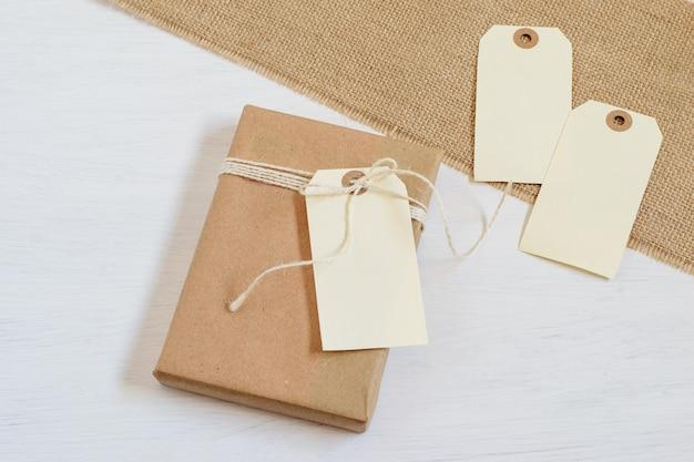 Draufsicht auf handgemachtes alternatives geschenk, das in recyceltem bastelpapier eingewickelt wird.
