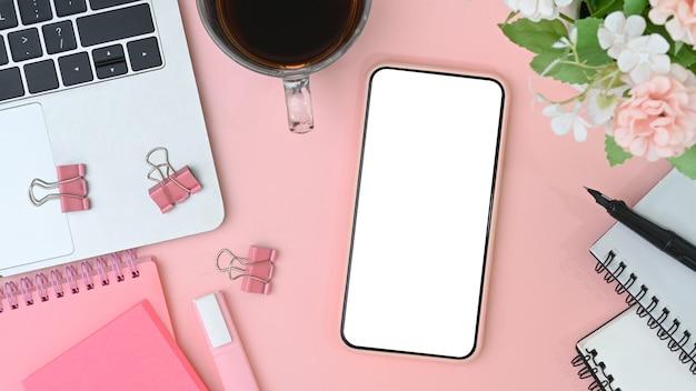 Draufsicht auf handy, laptop, kaffeetasse, notizbuch und blumen auf rosa hintergrund.