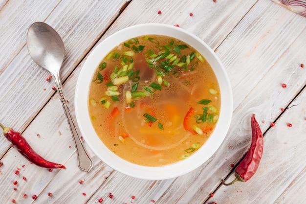 Draufsicht auf hausgemachte gemüsesuppe mit frühlingszwiebeln auf dem hellen holztisch