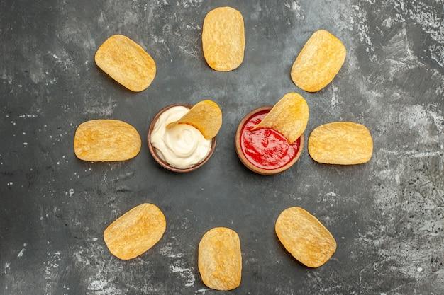 Draufsicht auf hausgemachte kartoffelchips, die in einem kreis und mayonnaise-ketchup auf grauem tisch angeordnet sind
