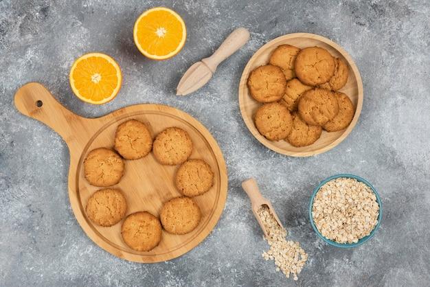 Draufsicht auf hausgemachte kekse auf holzbrett und haferflocken mit orangen über grauem tisch.