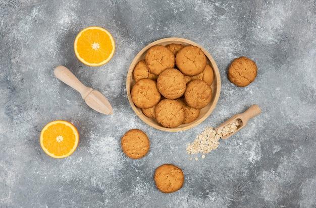 Draufsicht auf hausgemachte kekse auf holzbrett und haferflocken mit orangen über grauer oberfläche.