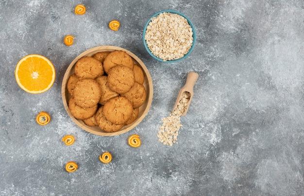 Draufsicht auf hausgemachte kekse auf holzbrett und haferflocken mit orangen.