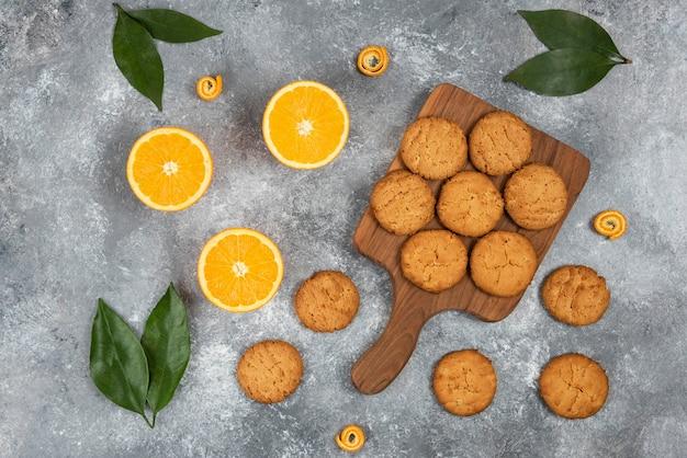 Draufsicht auf hausgemachte kekse auf schneidebrett aus holz und halbgeschnittene orangen mit blättern.