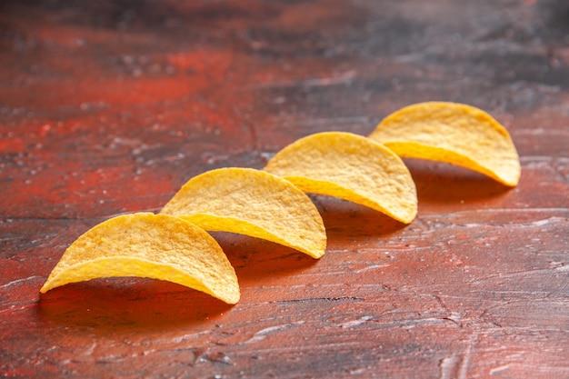Draufsicht auf hausgemachte köstliche vier knusprige chips, die auf dunklem hintergrund aufgereiht sind