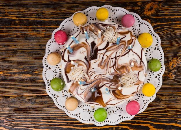Draufsicht auf hausgemachten geburtstagskuchen mit vielen brennenden kerzen in der nähe von verschiedenfarbigen macarons, auf holzschreibtisch