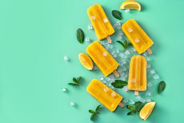 Draufsicht auf hausgemachtes veganes mango-eis am stiel auf trendigem aqua-menthe-hintergrund