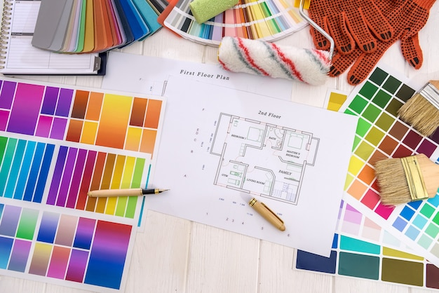 Draufsicht auf hausplan und bunte farbfelder auf holztisch