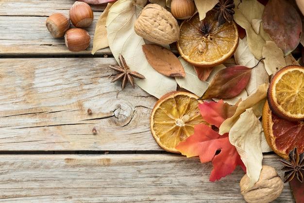 Draufsicht auf herbstblätter mit kastanien und getrockneten zitrusfrüchten
