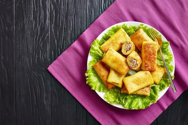 Draufsicht auf herzhafte crêpe-brötchen mit gemahlenem hühnerfleisch und champignonfüllung, serviert auf einem bad mit frischen salatblättern auf einem weißen teller