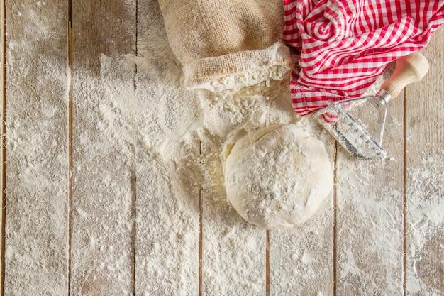 Draufsicht auf holzbretter mit mehl und teig