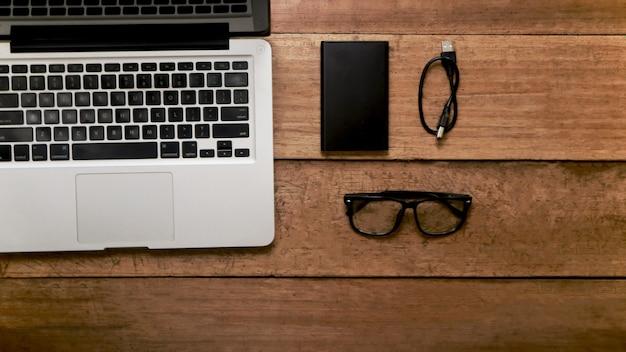 Draufsicht auf holzhintergrund mit laptop und externer festplatte
