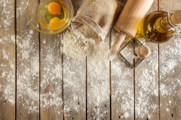Draufsicht auf holzoberfläche mit mehl, eiern und nudelholz