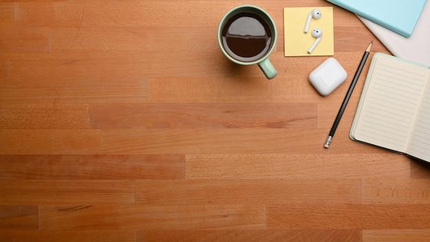 Draufsicht auf holztisch mit briefpapier, kaffeetasse und kopierraum im arbeitszimmer zu hause