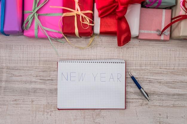 Draufsicht auf holztisch mit weihnachtsdekoration und notizblock mit dem wort