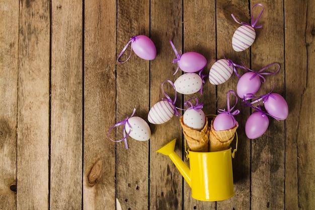Draufsicht auf holzuntergrund mit gießkanne und ostereier