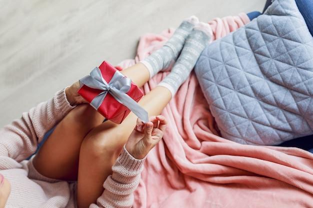 Draufsicht auf hübsche frau, die geschenkbox hält, auf sofa im haus sitzend. weiches foto. urlaubskonzept.