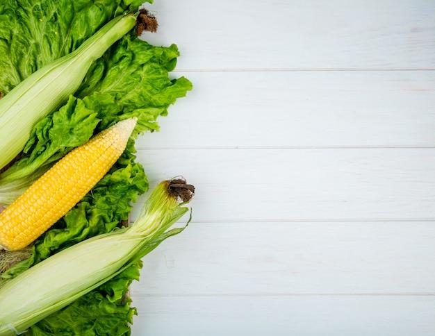 Draufsicht auf hühneraugen mit salat auf der linken seite und weiß mit kopierraum