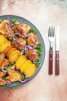 Draufsicht auf hühnerflügelplatte von kartoffeln hühnerkräuter zwiebelgabelmesser