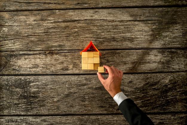 Draufsicht auf immobilien oder versicherungsagenten, die ein haus aus einem holzwürfel bauen