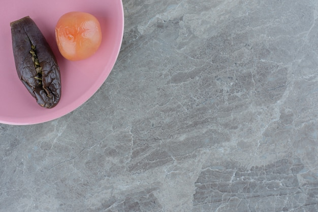 Draufsicht auf in essig eingelegte auberginen und tomaten auf orangefarbenem teller über grauem hintergrund.