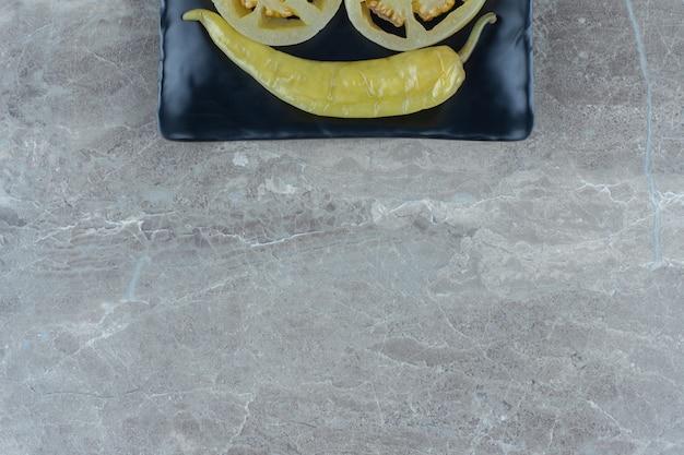 Draufsicht auf in essig eingelegte peperoni auf schwarzem teller über grauem hintergrund.