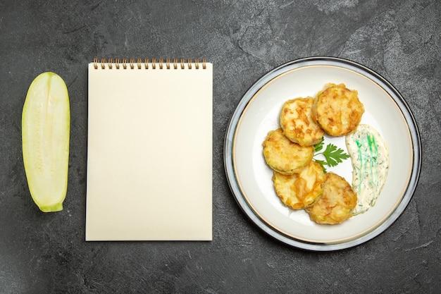 Draufsicht auf in scheiben geschnittenes gemüse der leckeren kürbismahlzeit innerhalb der platte auf grauer oberfläche