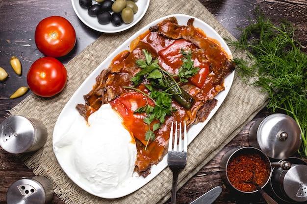 Draufsicht auf iskender-kebab, garniert mit tomate und petersilie, serviert mit joghurt
