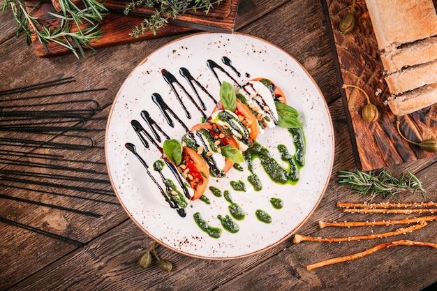 Draufsicht auf italienischen caprese-salat mit pesto-soße auf dem holztisch