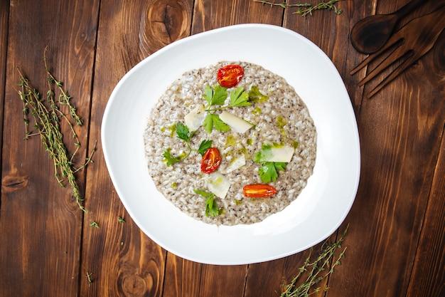 Draufsicht auf italienisches risotto mit trüffelsauce olivenöl und tomaten