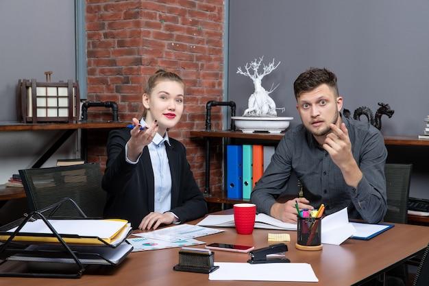 Draufsicht auf junge beschäftigte büroangestellte, die ein wichtiges thema im büro diskutieren discuss
