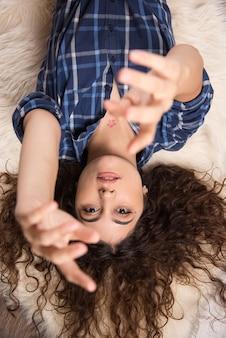 Draufsicht auf junge frau, die auf teppich liegt