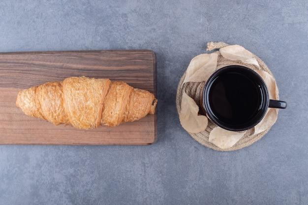 Draufsicht auf kaffee und croissants. klassisches französisches frühstück auf grauem hintergrund.