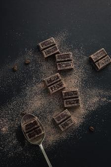 Draufsicht auf kaffeebohnen und dunkle schokoladenstücke, die mit kakaopulver bestreut sind