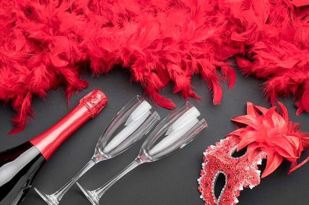 Draufsicht auf karnevalsmasken mit federn und champagnerflasche
