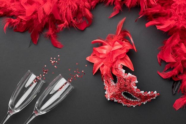 Draufsicht auf karnevalsmasken mit federn und champagnergläsern