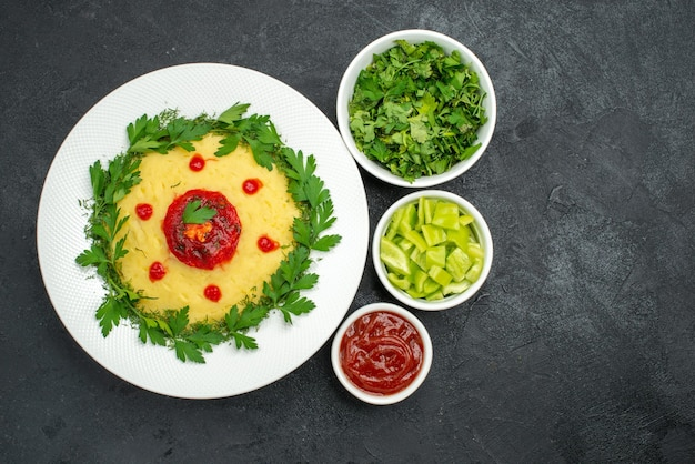 Draufsicht auf kartoffelbrei mit tomatensauce und grüns auf dunkelheit